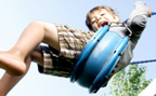 Young boy pumps high on swing