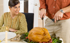 Woman watches man carve turkey at table